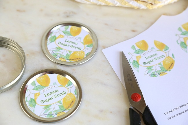 gluing lemon sugar scrub labels on caps