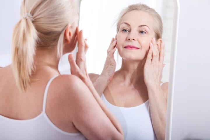 collagen benefits for skin, older woman in mirror